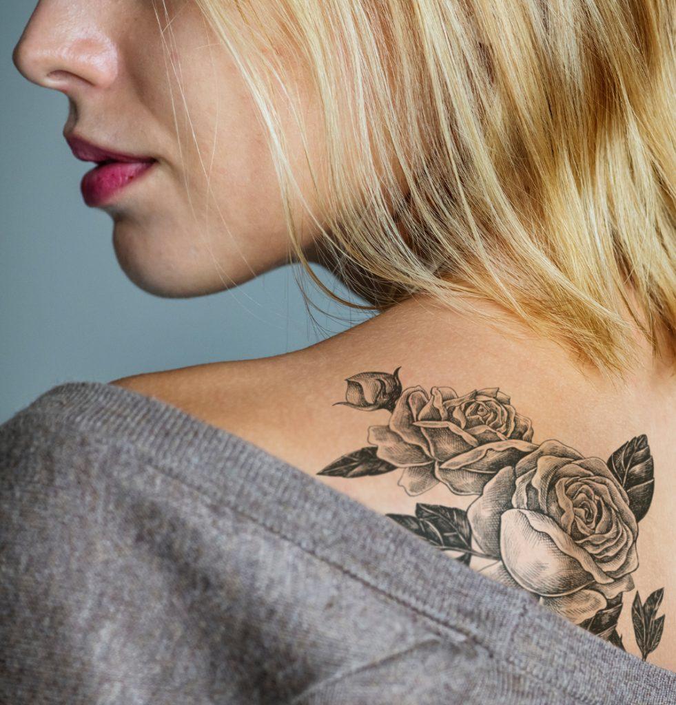 Woman with tattoo on upper back, head turned to side, upclose