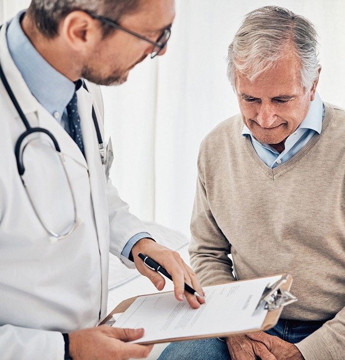 Male doctor with clipboard speaking with older man