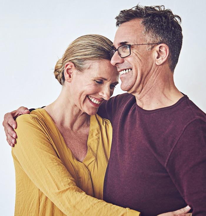 Older woman and older man hugging each other, smiling together